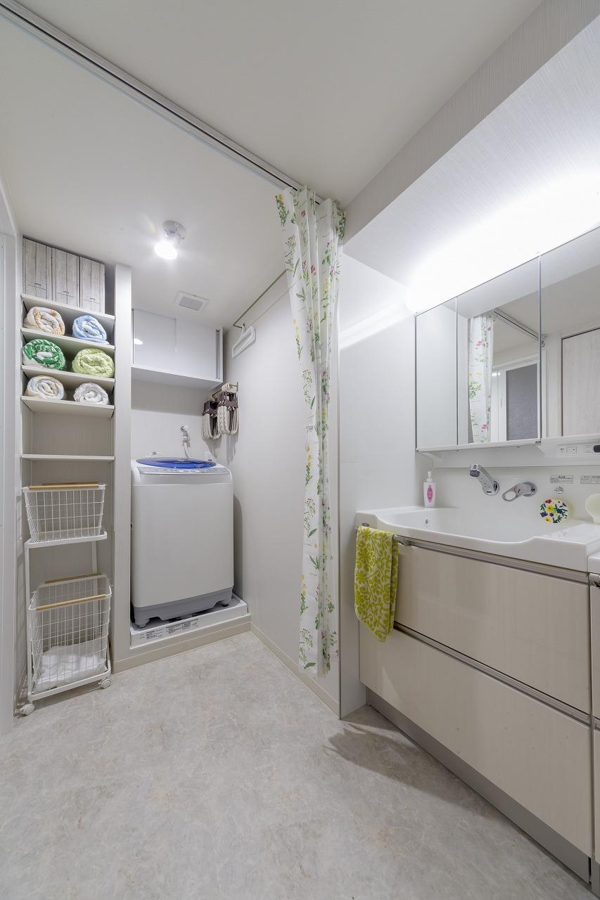 洗面台の周りの壁はメンテナンスが楽なキッチンパネルで囲み、洗濯機横のパイプスペースには可動棚を設置。