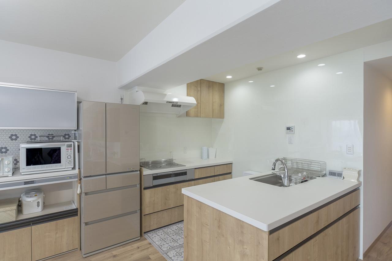 家族数人で立ってもゆとりのあるキッチン。メンテナンスしやすいキッチンパネルをコーナー壁に広く貼りました。