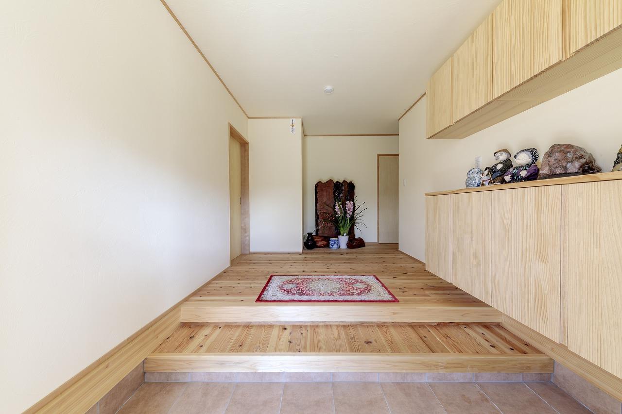 上がり框と床の縦横の木目が美しい玄関ホール。玄関収納は木目の凹凸を活かした浮造りに。