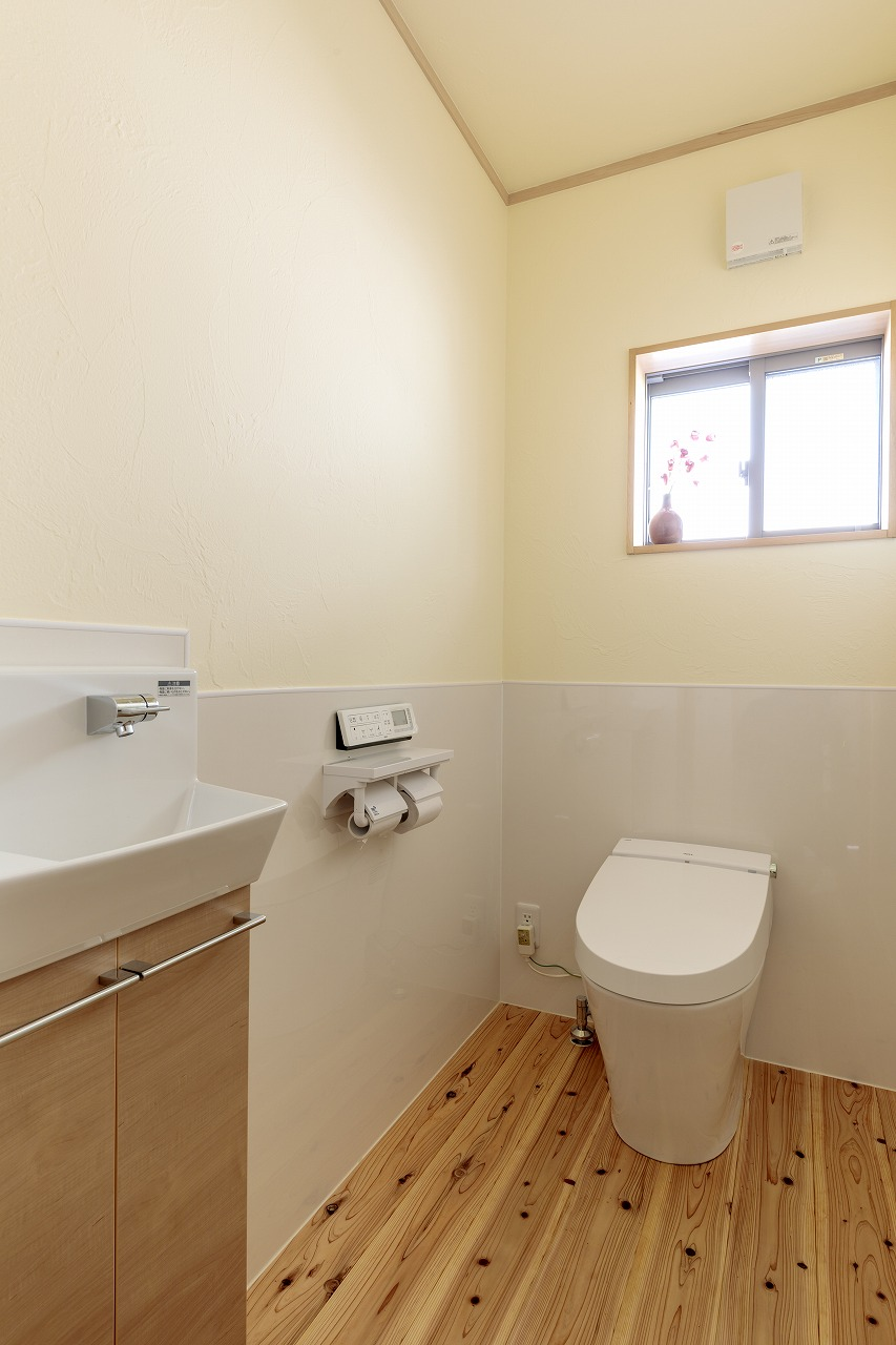 トイレ内も消臭力のある珪藻土の塗り壁と杉無垢床で仕上げました。腰壁は手入れしやすいキッチンパネルに。