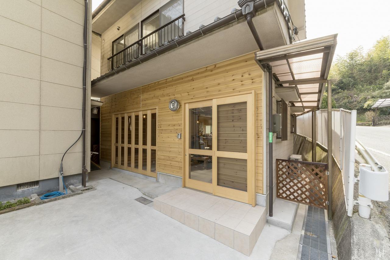 杉板を貼った玄関。左側の扉は折りたたみ式で大きく開くことができます。