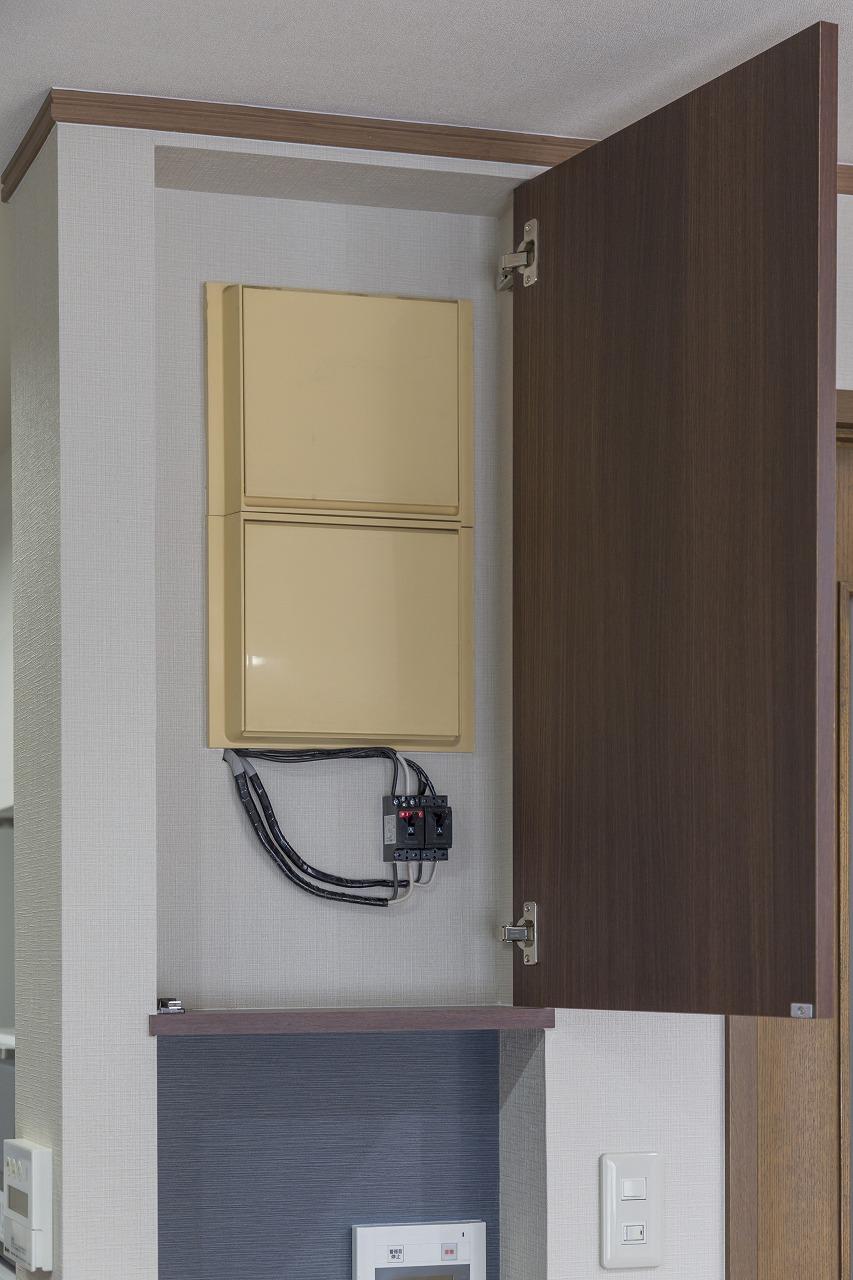 劣化して黄ばみが気になっていた分電盤は、壁を掘り下げ、開閉式の扉をつけてすっきりとした飾り棚に。