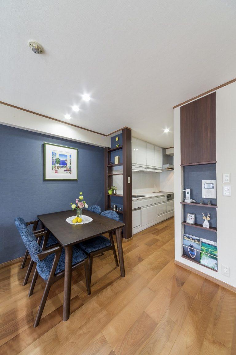 壁の一面をスタイリッシュなブルーのアクセントウォールに。キッチンとの仕切り壁はインテリアを楽しむ飾り棚に。