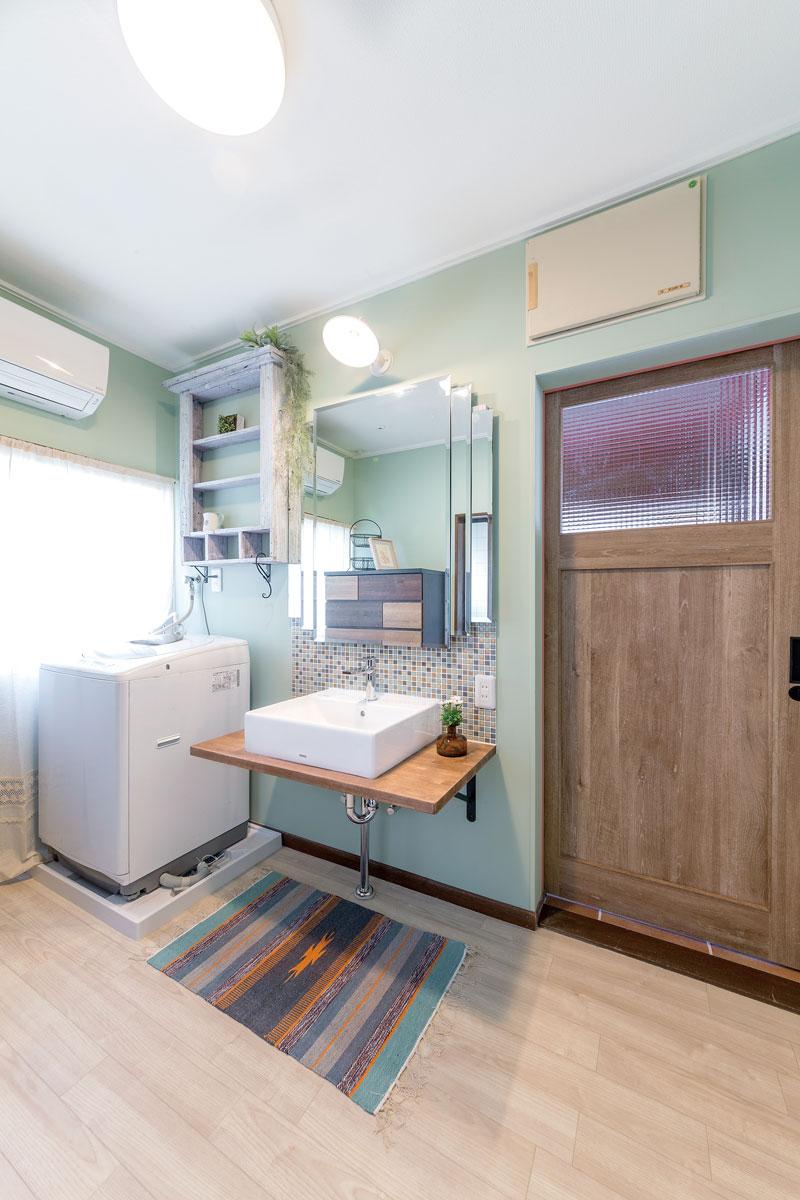 淡いグリーンに塗装した爽やかな印象の洗面室。持っていた鏡や棚を上手に使って自分らしい空間に。