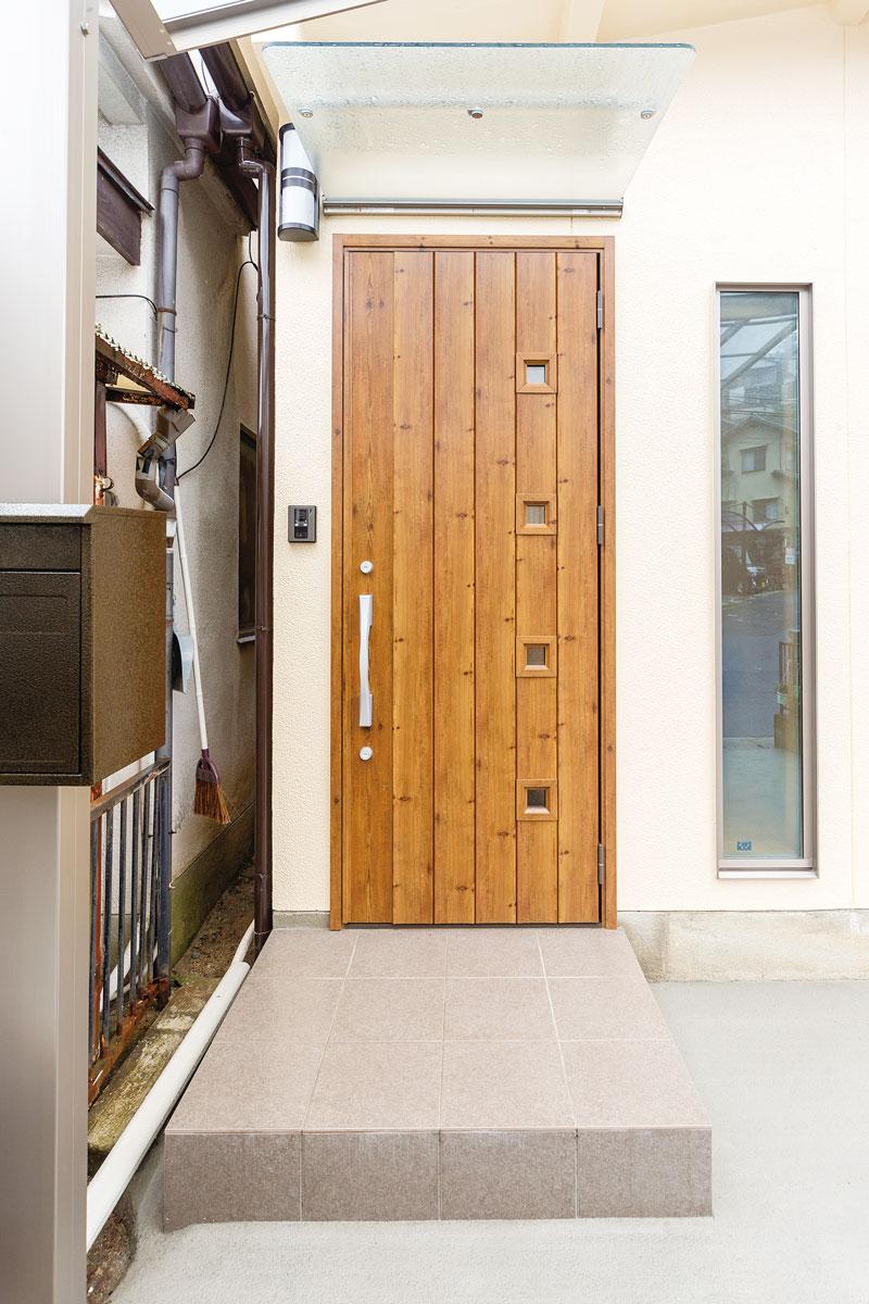 木のぬくもりを感じる玄関ドア。ガラスタイプの庇にしたことで、光が通り、より明るい印象に。