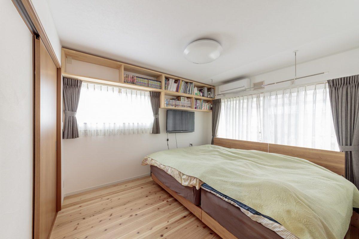 家族4人で寝られる広めの寝室。壁には本棚を造りつけて空間を有効活用。