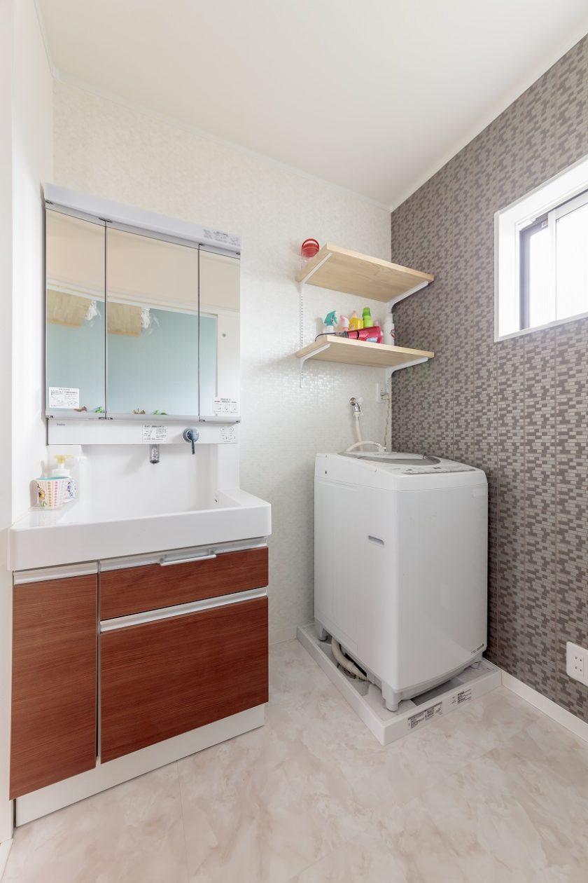 クロスや床、洗面台を落ち着いた色で統一した洗面室は、自然光の入る優しい雰囲気。