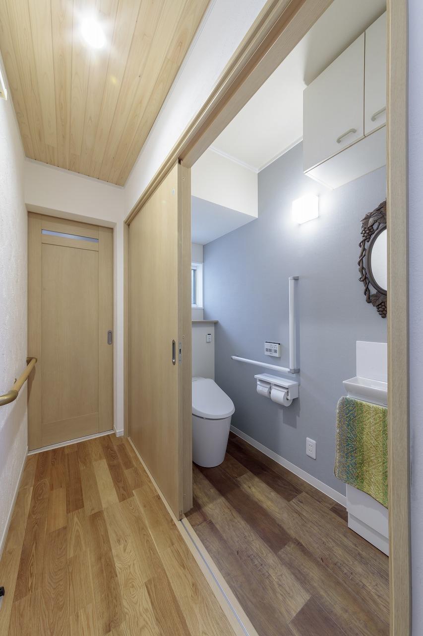 1階トイレは車椅子でも出入りできる大きく開閉する引き戸。上部に収納も設置。