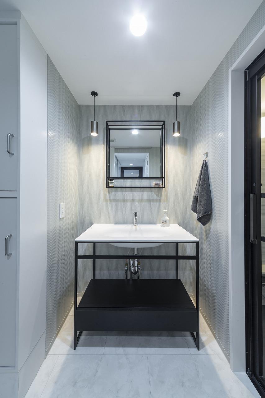 シックなテイストでまとめた洗面所。光沢のあるクロスが照明の光を受け輝き、上品な華やかさを演出。