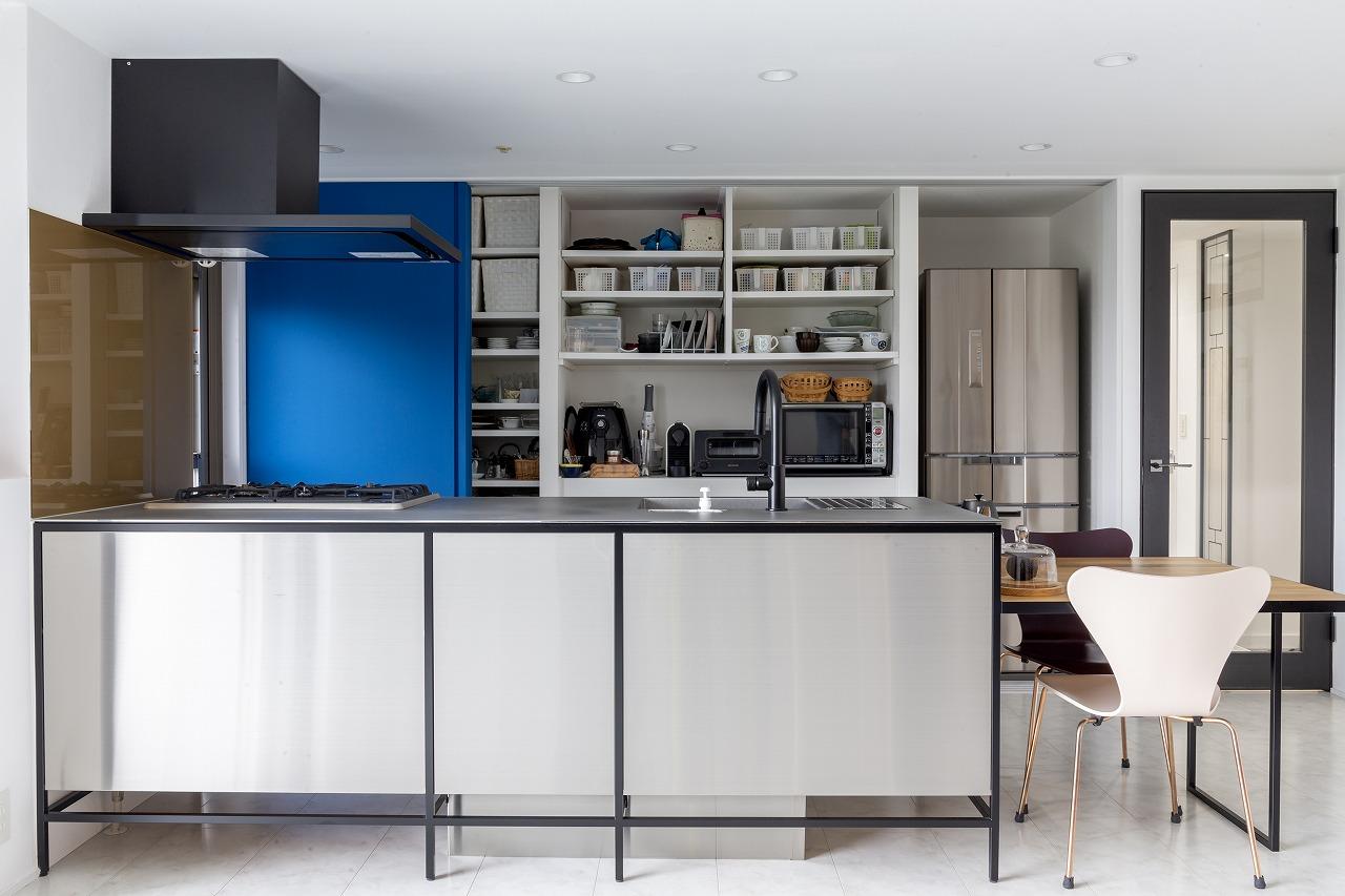 ブルーの扉をスライドさせると現れる、床から天井まであるパントリーは、家電に合わせたジャストサイズの棚を造作。