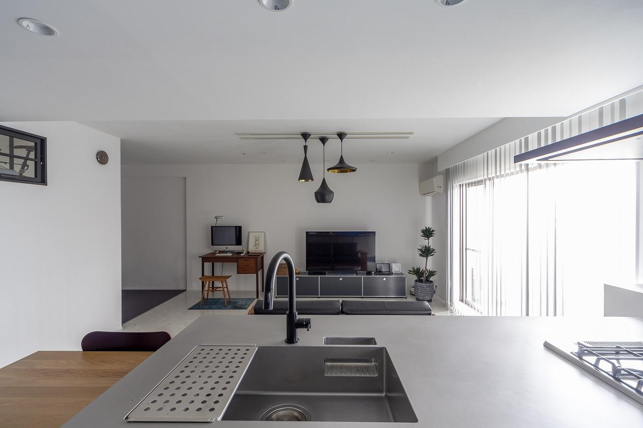 キッチン側から見たLD。壁は漆喰。フォルム違いのペンダントライトが空間のアクセントに。