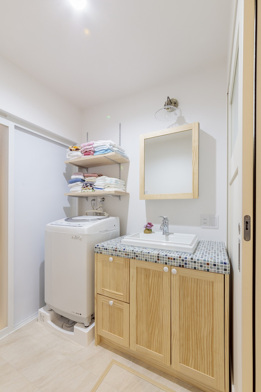 木目とタイルがかわいい洗面台。レトロな照明もご主人のチョイス。