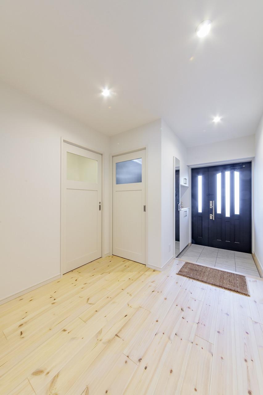 玄関から伸びる廊下をなくし、広いホールに。右のドアはWIC、左のドアはトイレです。