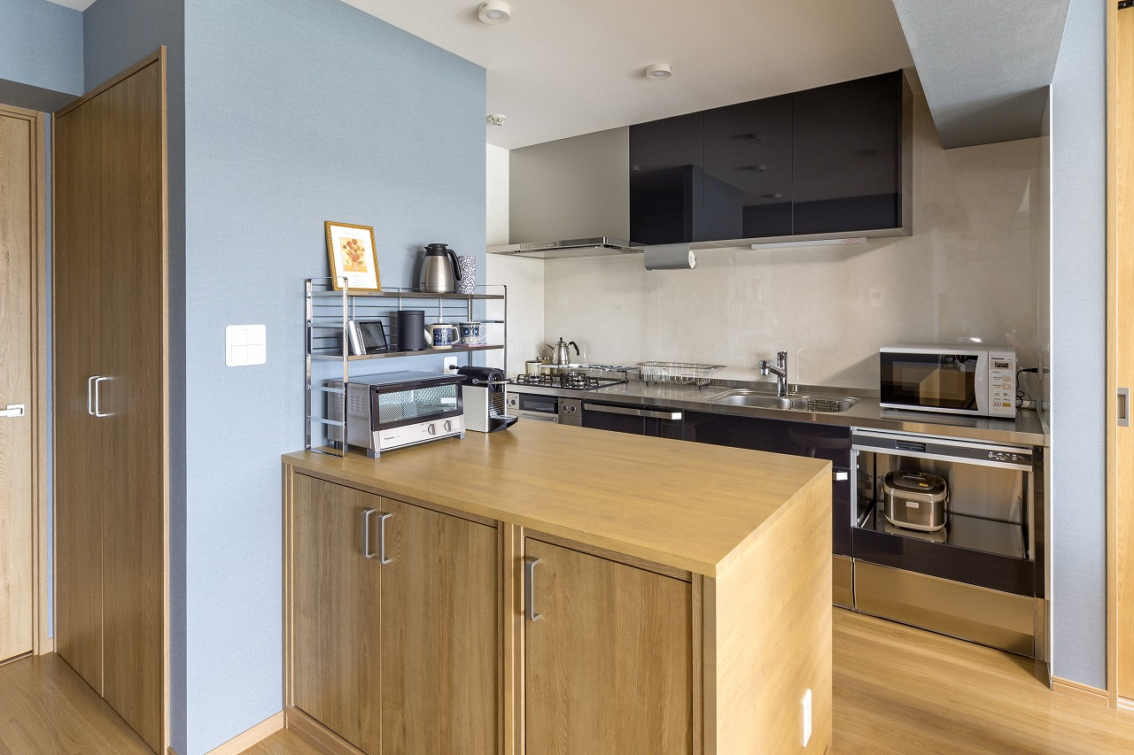 キッチンには使い勝手のよいワークカウンターを造作。冷蔵庫の背面(写真左手)には、掃除機などが入る収納を設け、限りあるスペースを有効活用しています。