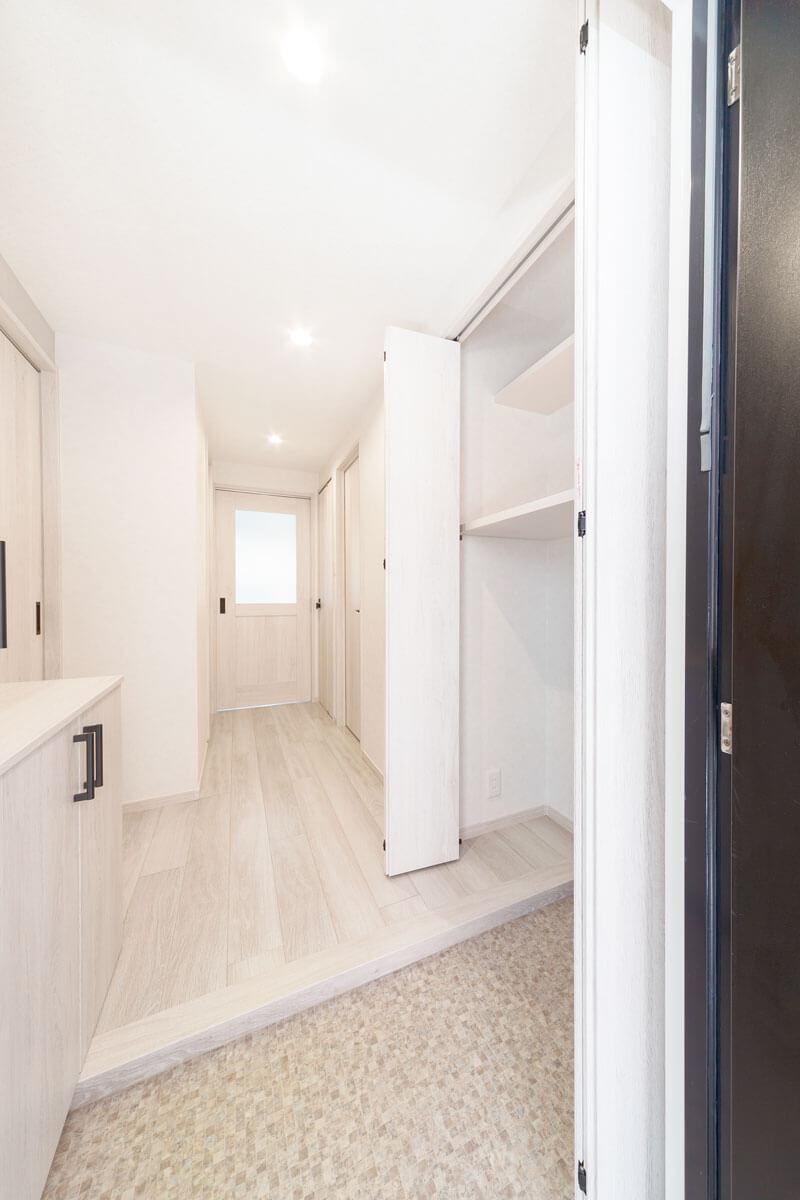 玄関脇の部屋の一角を玄関側のスペースとし、大型収納を設置。