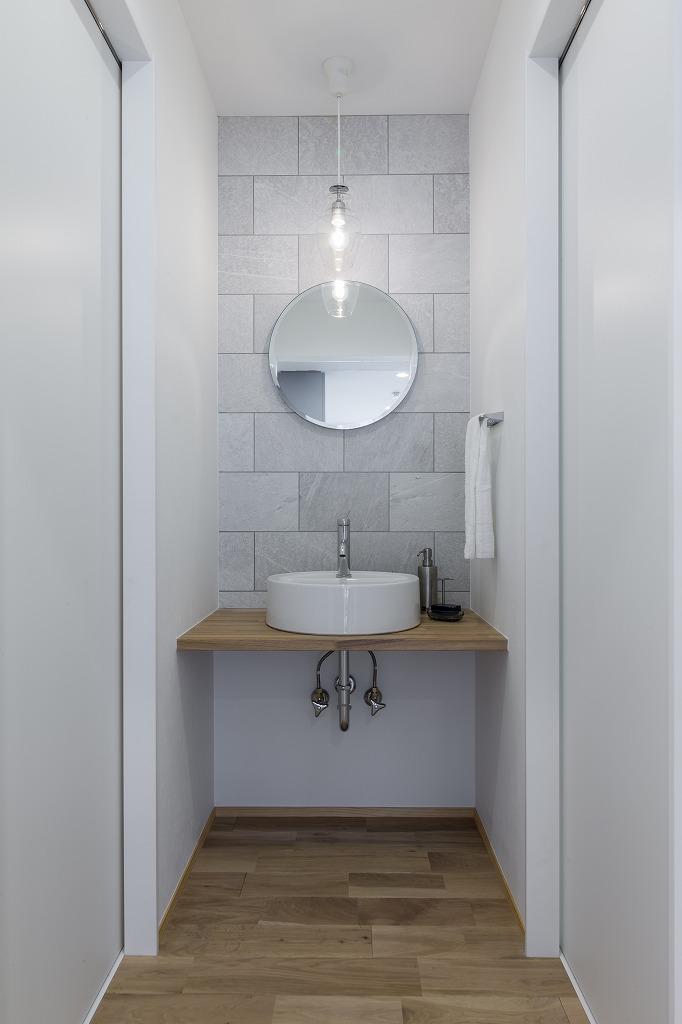 ゲスト用の洗面台。セメント調レリーフのデザインタイルでやわらかい印象に。