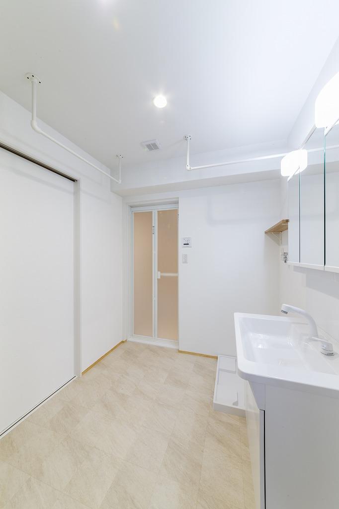洗面室には洗濯物をかけるハンガーパイプを設置。壁の1面は調湿性のあるスイス漆喰。