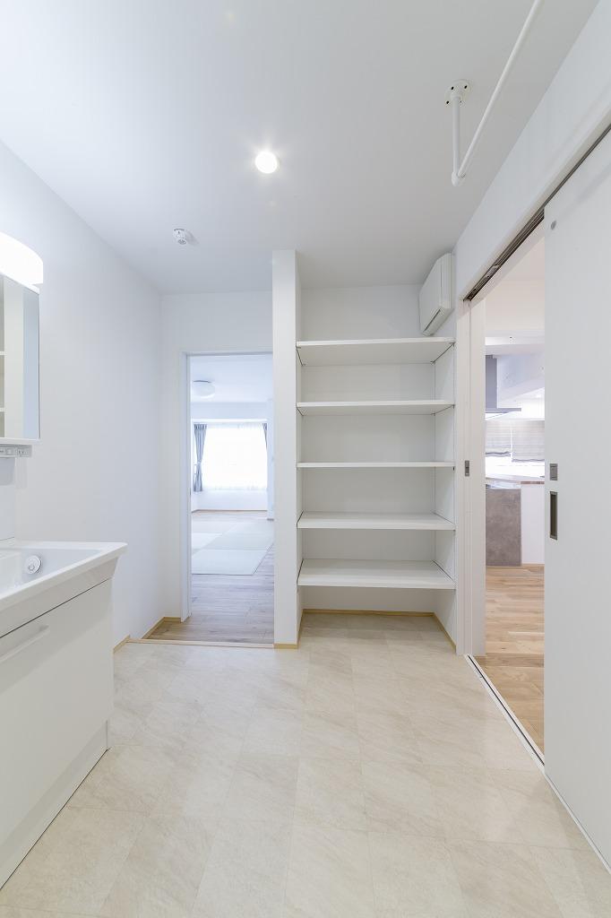 LDK(右扉)や寝室(左扉)とつながるランドリールーム兼家族用の洗面室。