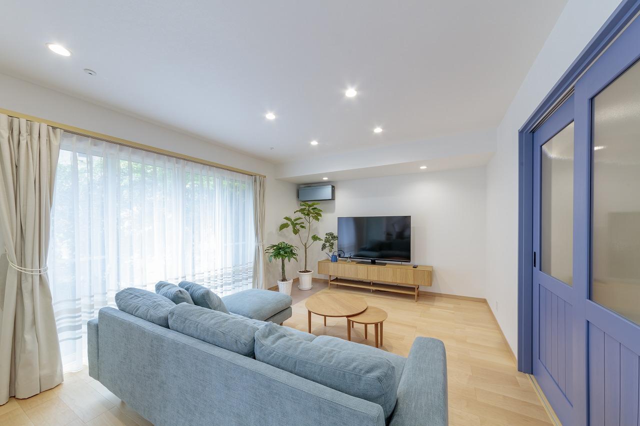 廊下に面したドアはアクセントカラーのブルーに塗装。掃き出し窓側の天井には室内干し用の金具を設置。
