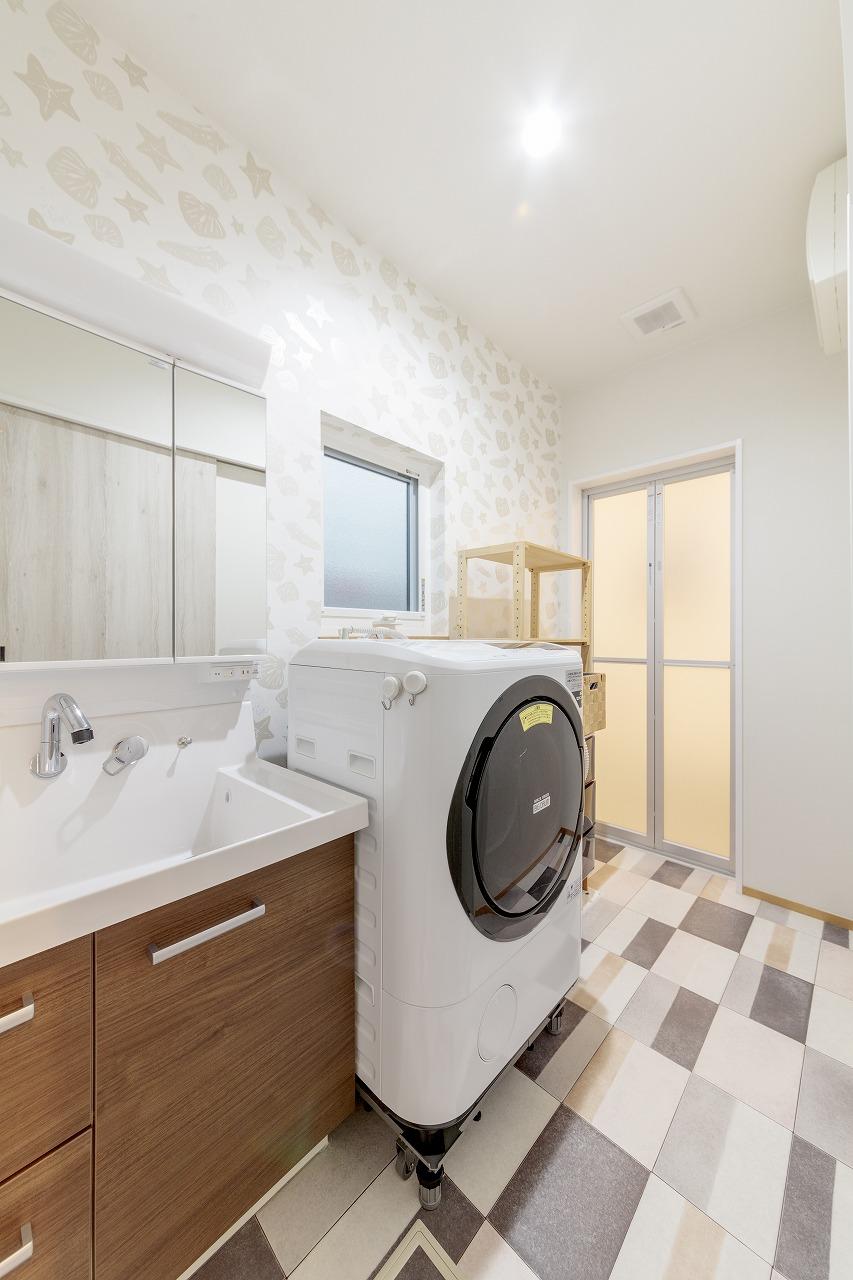 クロス選びを楽しんだ洗面室。貝殻のデザインクロスと大胆なパターンのクッションフロアをチョイス。