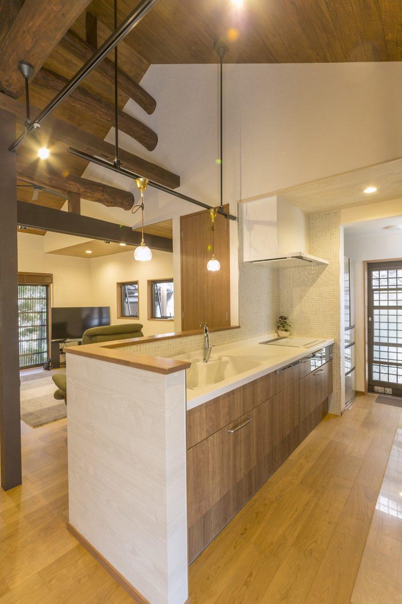 対面式にしたキッチンは部屋になじむ木目調のパネルにタイルでアクセントを。