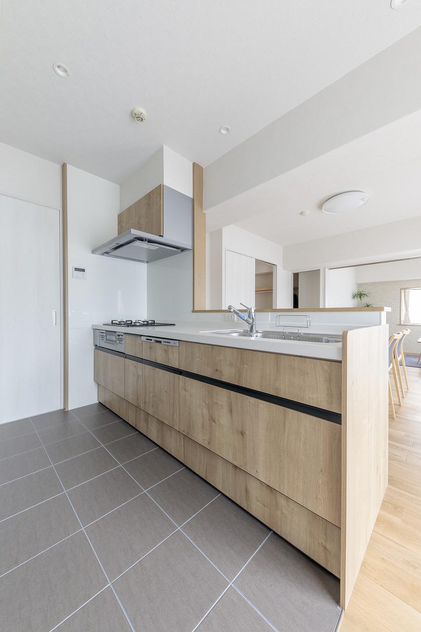 白色と明るい木目調で統一したキッチン。床は傷のつきにくいタイルを敷きました。