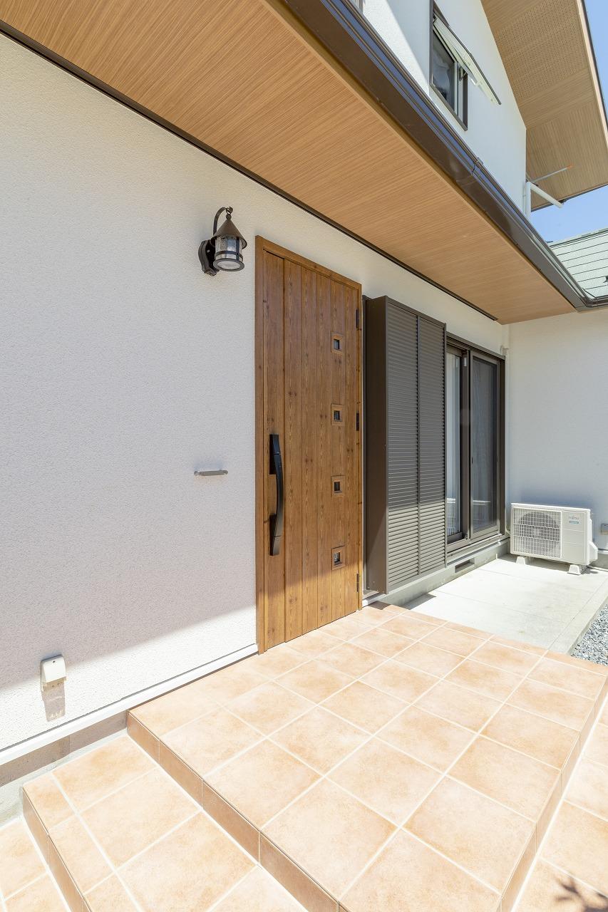 玄関ドアやサッシは断熱性の高い製品に新調。庇部分の木目柄の軒天がおしゃれな印象に。