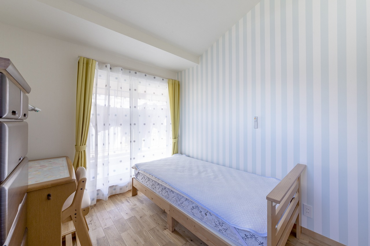 勾配天井を見せた子ども部屋。アクセントクロスとカーテンが爽やかな印象です。