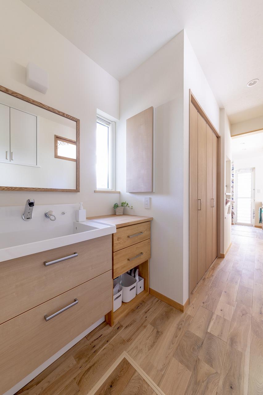 玄関からキッチンへ抜ける裏動線上に洗面が。収納を造作して使い勝手の良さに配慮。