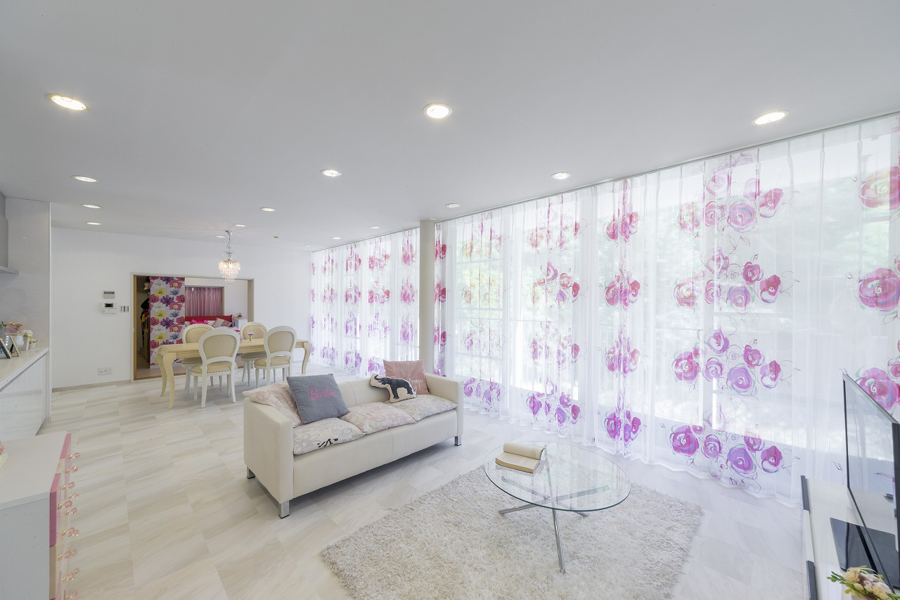 床は白い石目調のフロアタイルを追い貼りしています。広さのある窓に大胆な花柄カーテンが映えます。
