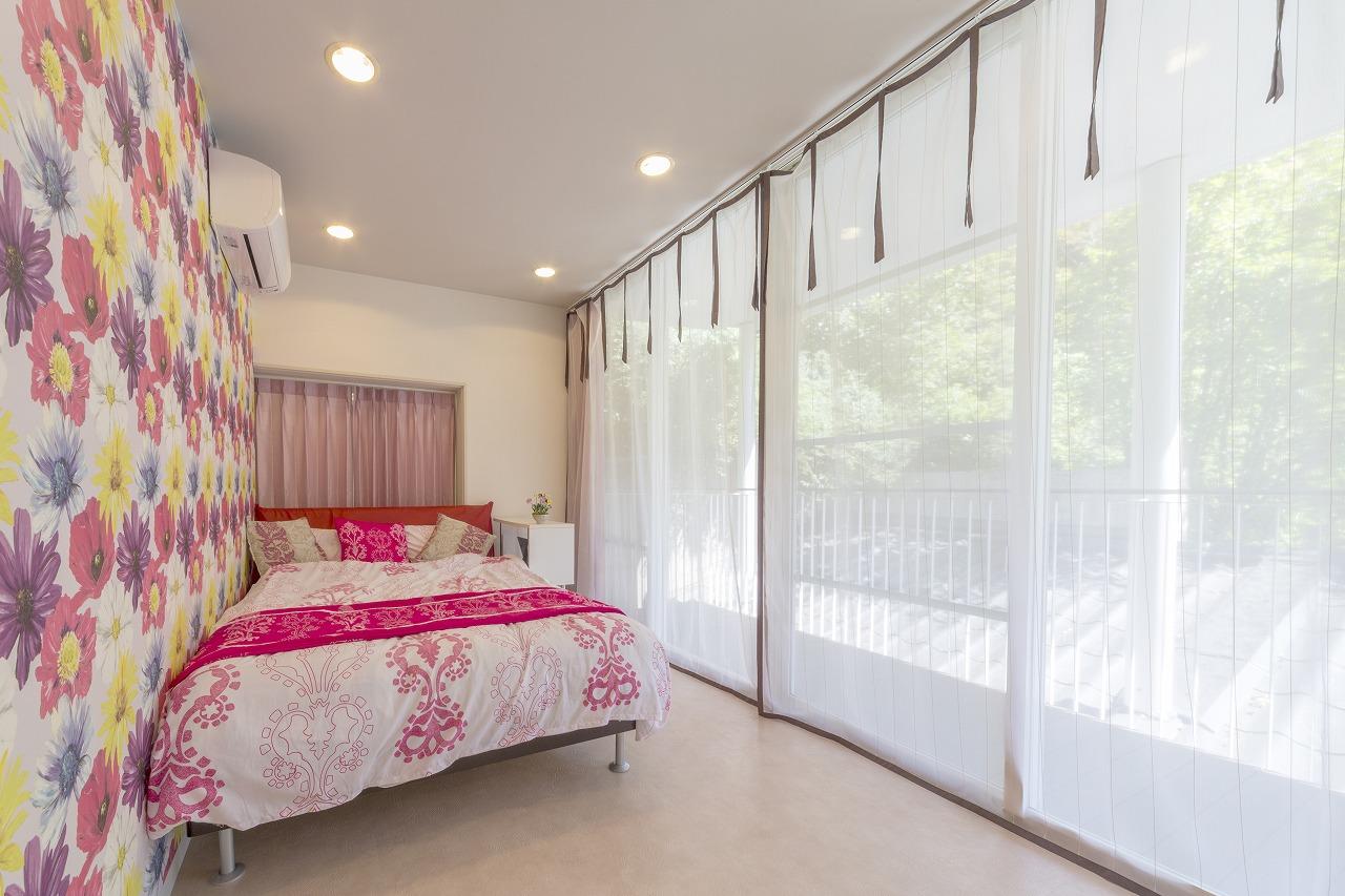 畳敷きの和室をフロアタイルにした寝室。鮮やかな花柄のアクセントクロスは奥さまのお気に入り。