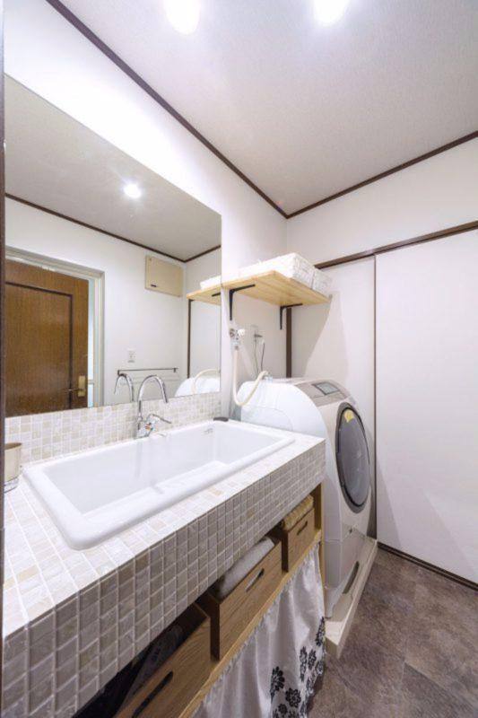 実験用の大型シンクと一枚ガラスの鏡を設置したおしゃれな洗面脱衣室。