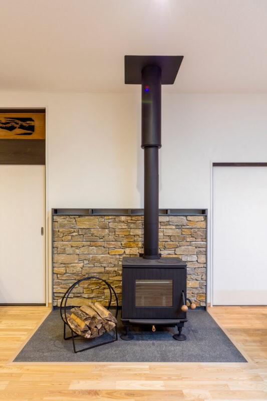 薪ストーブの床には天然石を採用。背面はストーブの熱が逃げるように通気口を設けています。