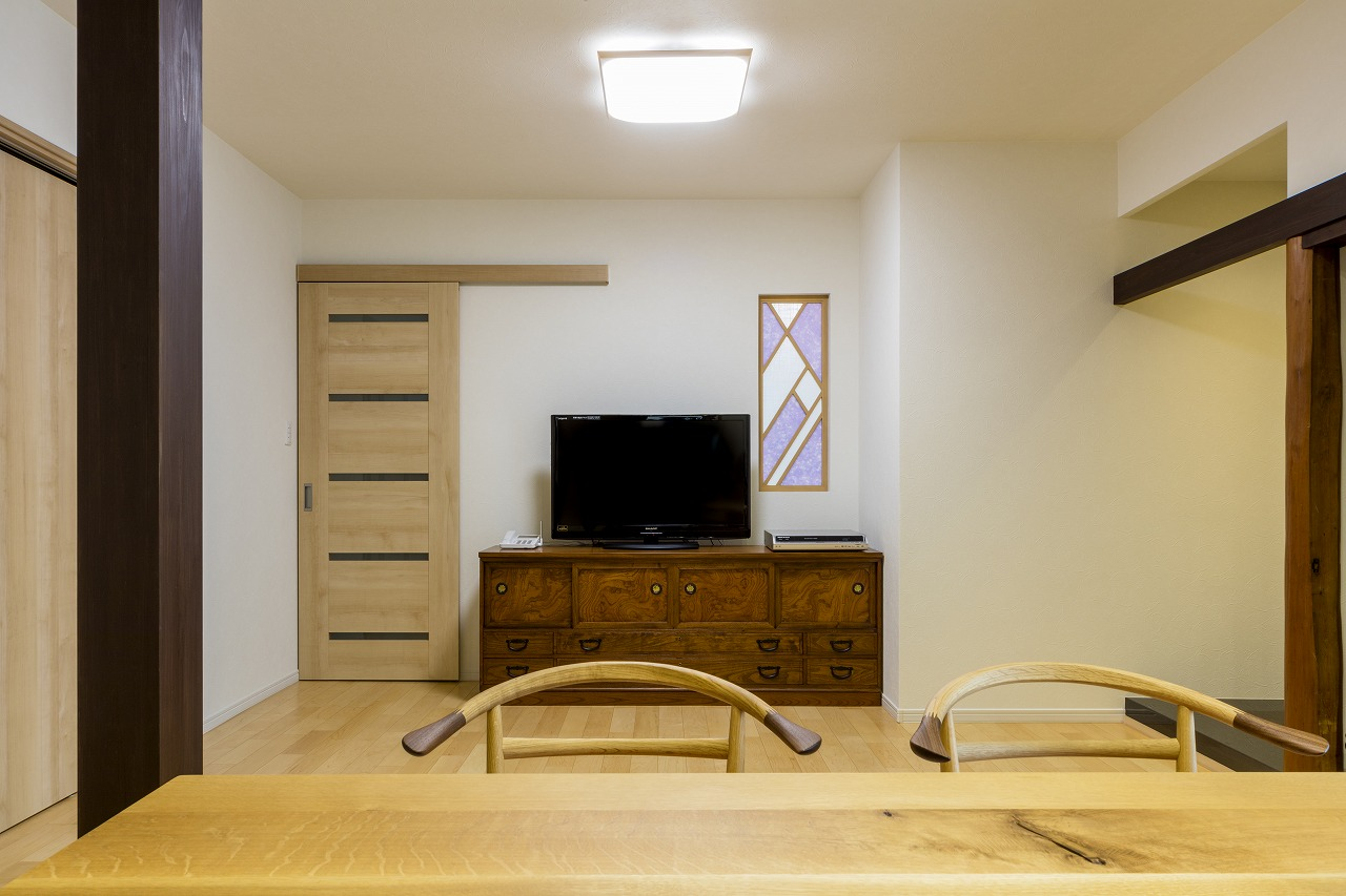 LDKと寝室を仕切る壁に施主さまの名字をデザインしたオリジナルの明り取り窓を設置。