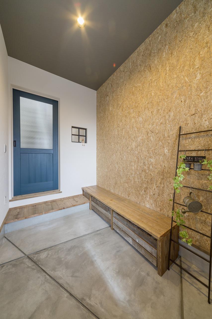 玄関の床はコンクリート、壁はOSBボードで仕上げ、下部収納つきの足場板のベンチをオーダー。