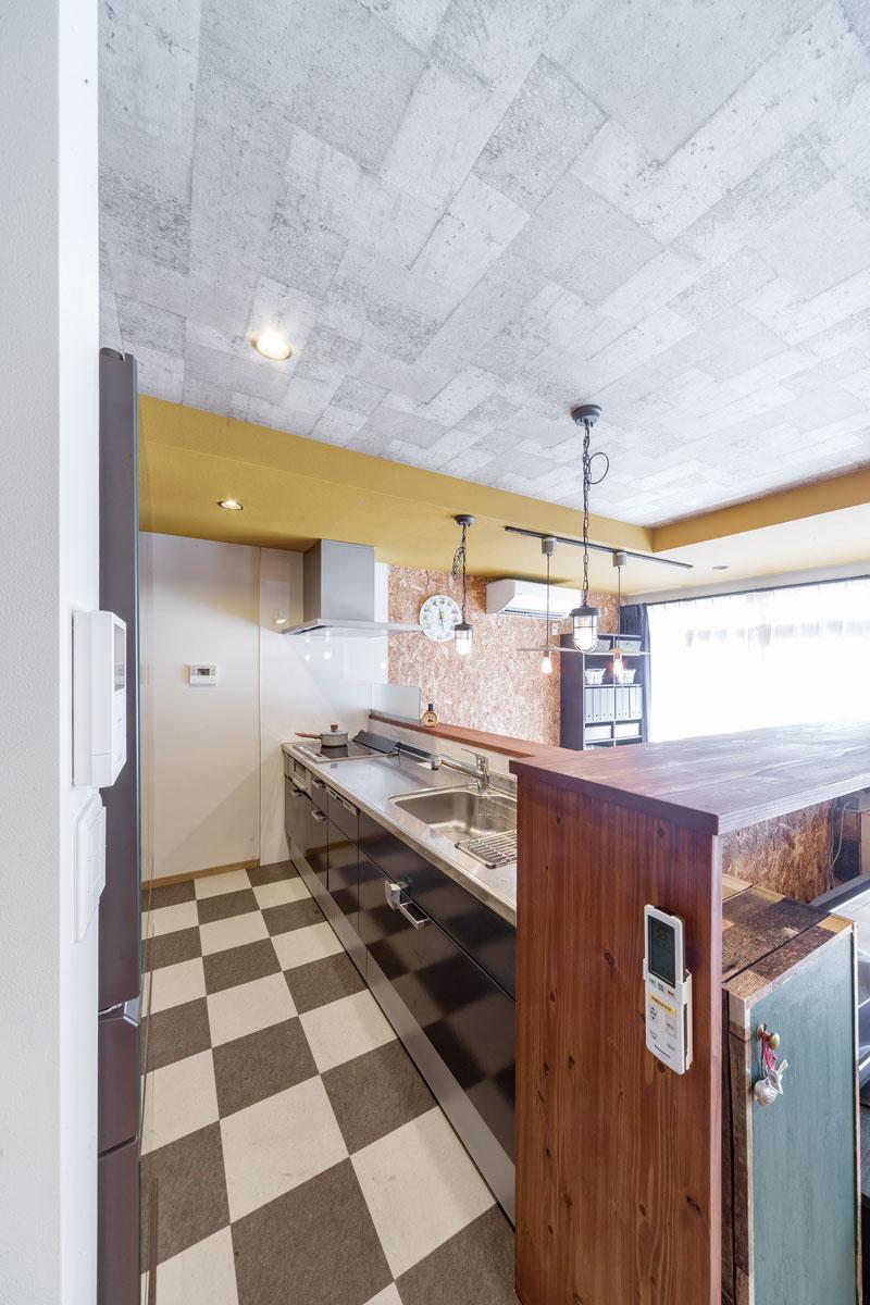 キッチンの向こう側にダイニングテーブルがある便利な対面式。床は水や汚れに強いタイルカーペットを選びました。