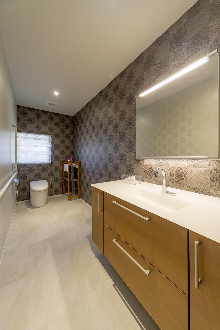 手洗いを広く設け、手すりを設置した落ち着いた雰囲気の家族用トイレ。