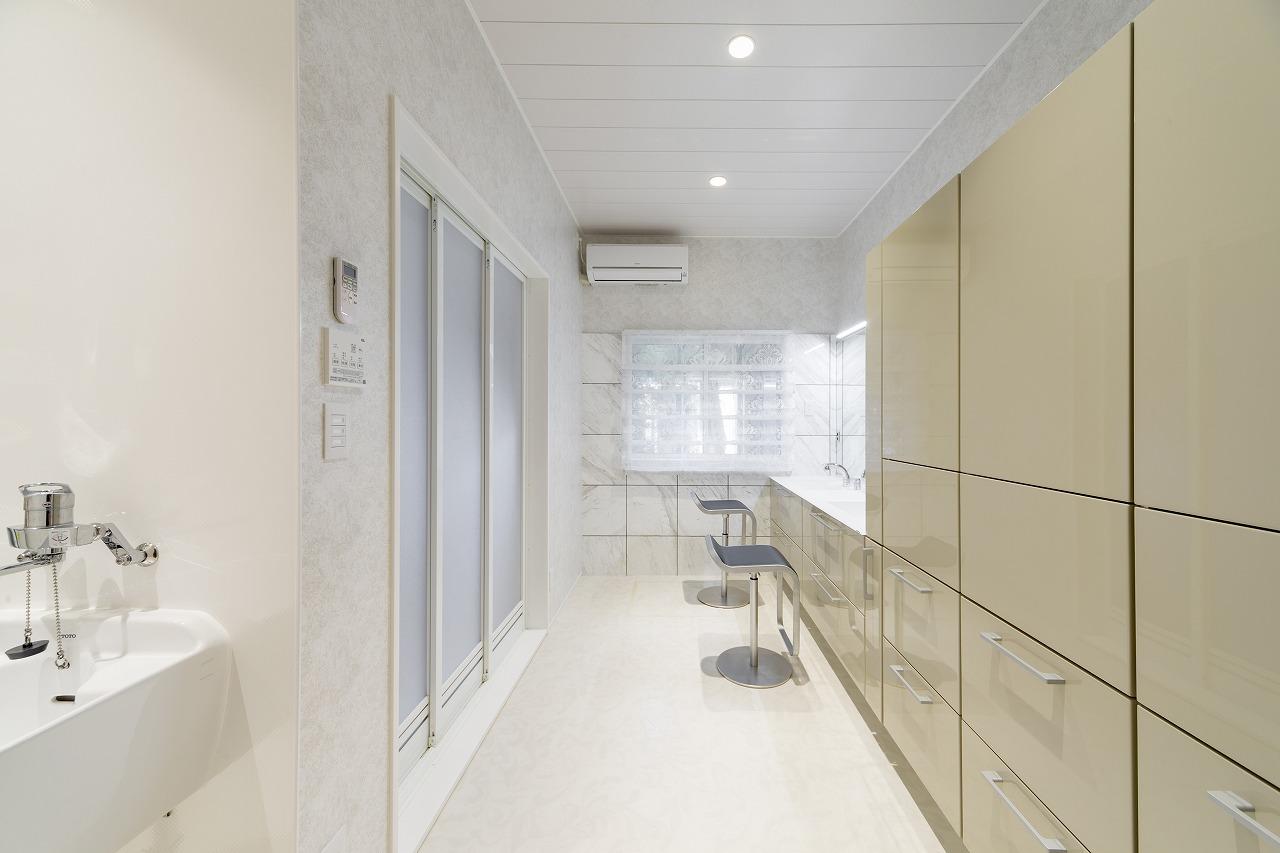 白で囲まれたパウダールームは照明の色を切り替えられます。窓側の壁には水散りを考慮して大理石を設置。