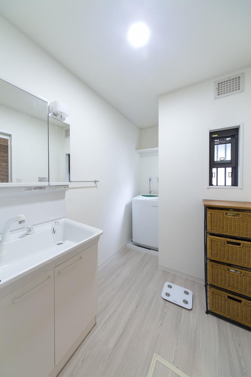 浴室を広げるため壁を移動させた洗面室は広くなり、奥まったスペースは洗濯機の置ける無駄のない空間となりました。