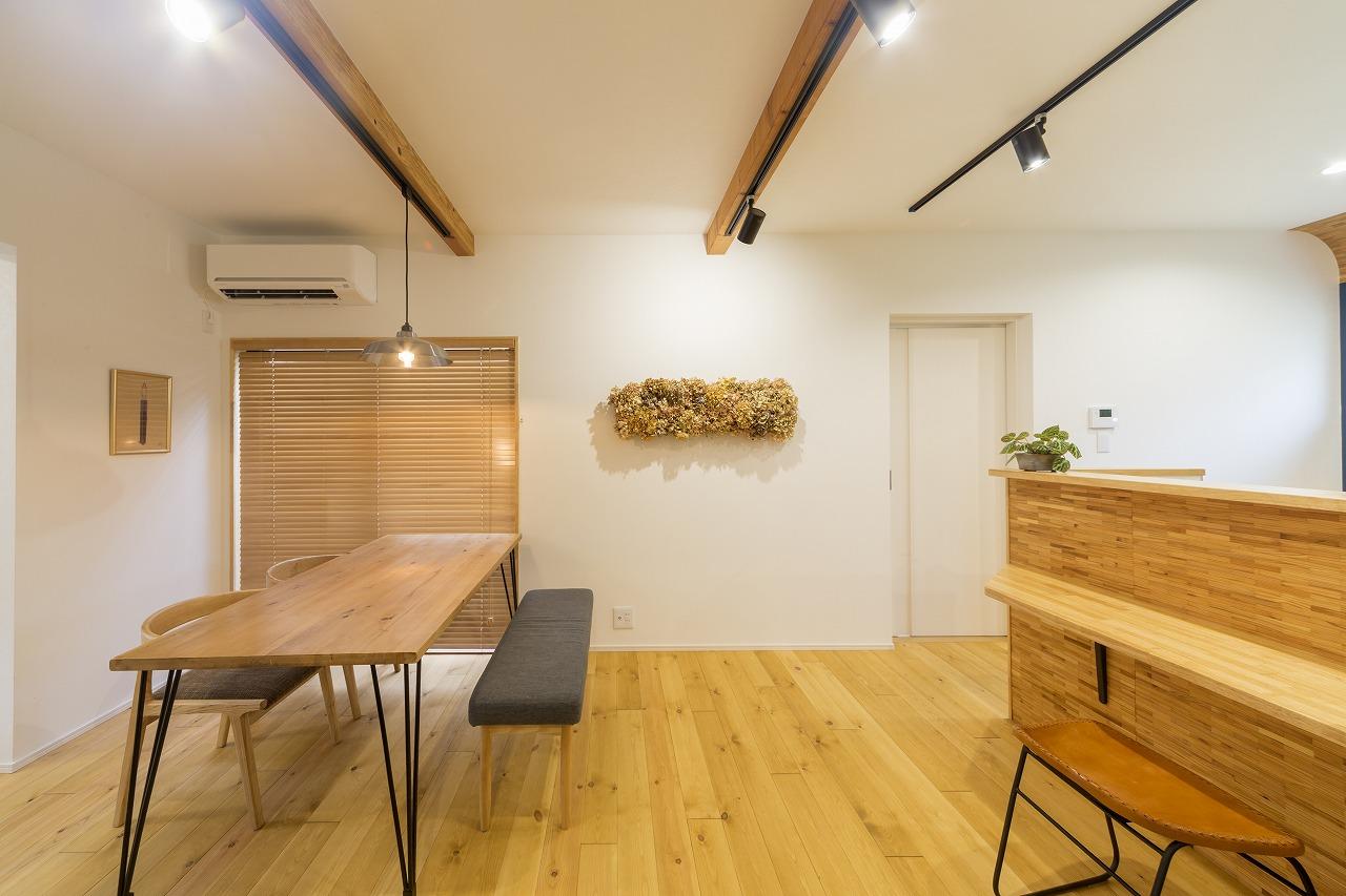 杉の間伐材を使った木製タイルのカウンターと床色、ライティングが調和するダイニング空間。