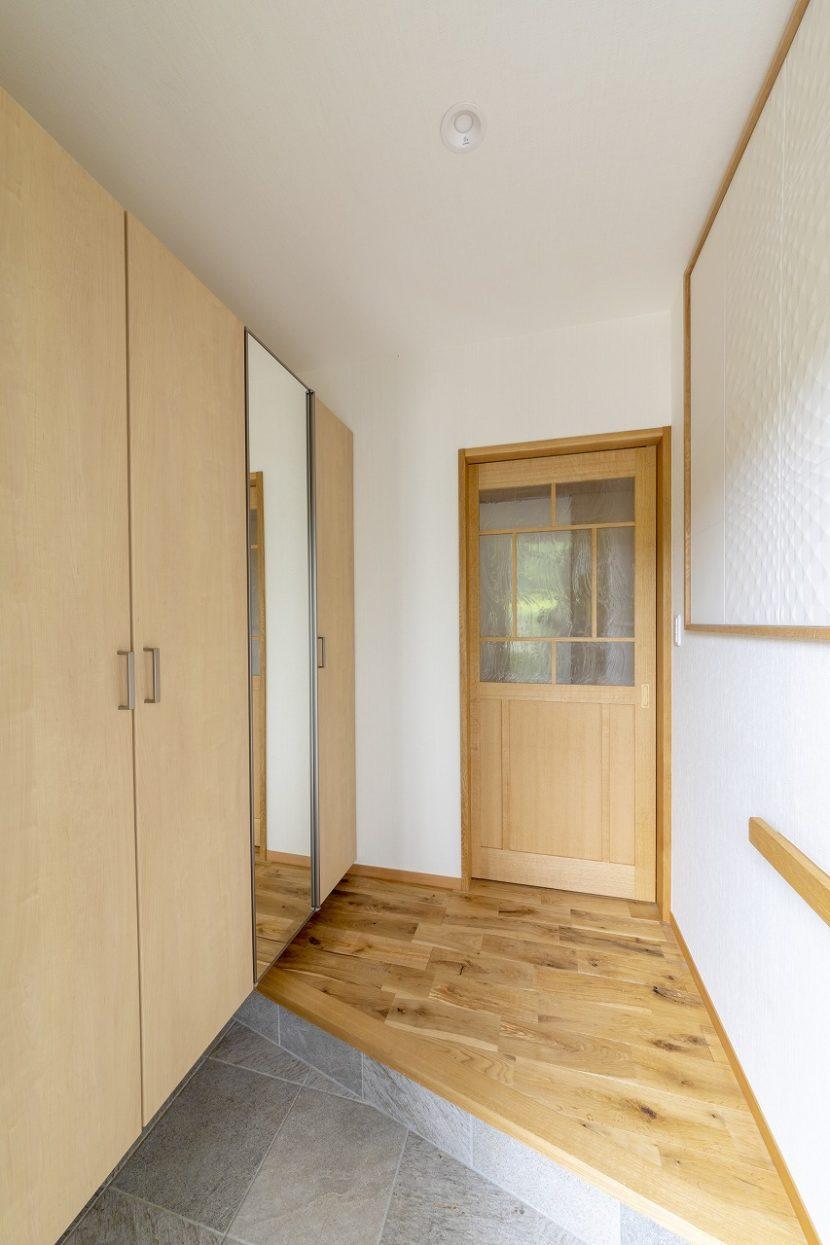 斜め框で土間を広くした玄関。輸入ガラスの引き戸が空間を引き立てます。