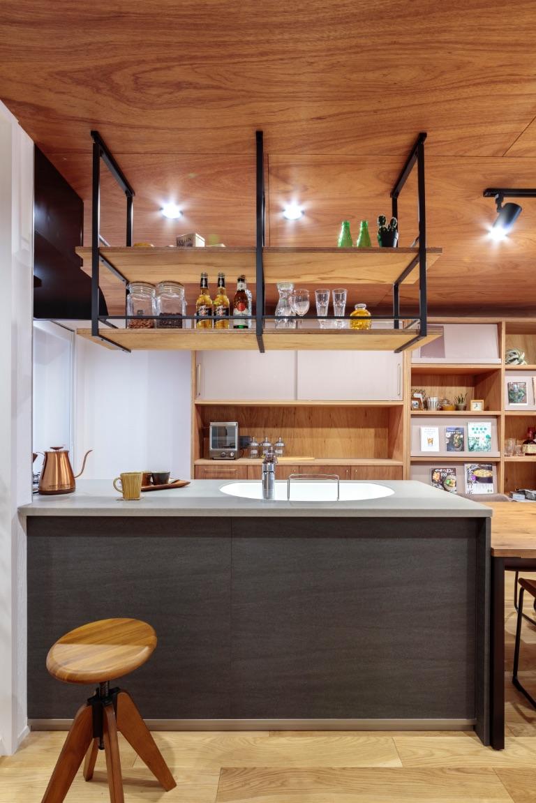 アートのようなトクラスのキッチンを壁に埋め込むように設置。吊り棚はラワンベニヤで造作。