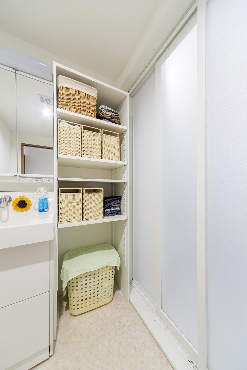 洗面室が広くなった幅に合わせて棚を設置。浴室のドアは開口部の広い3枚引き戸を採用。