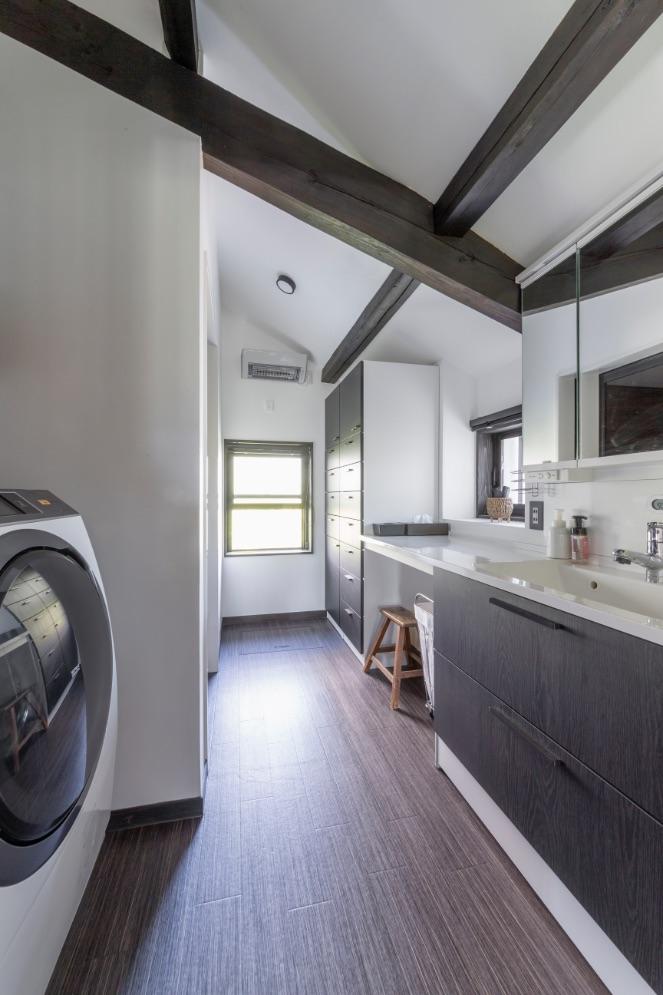 ゆとりのある洗面室は、勾配天井の高さに合わせたチェストを設置。窓の上には暖房乾燥機も取りつけ。