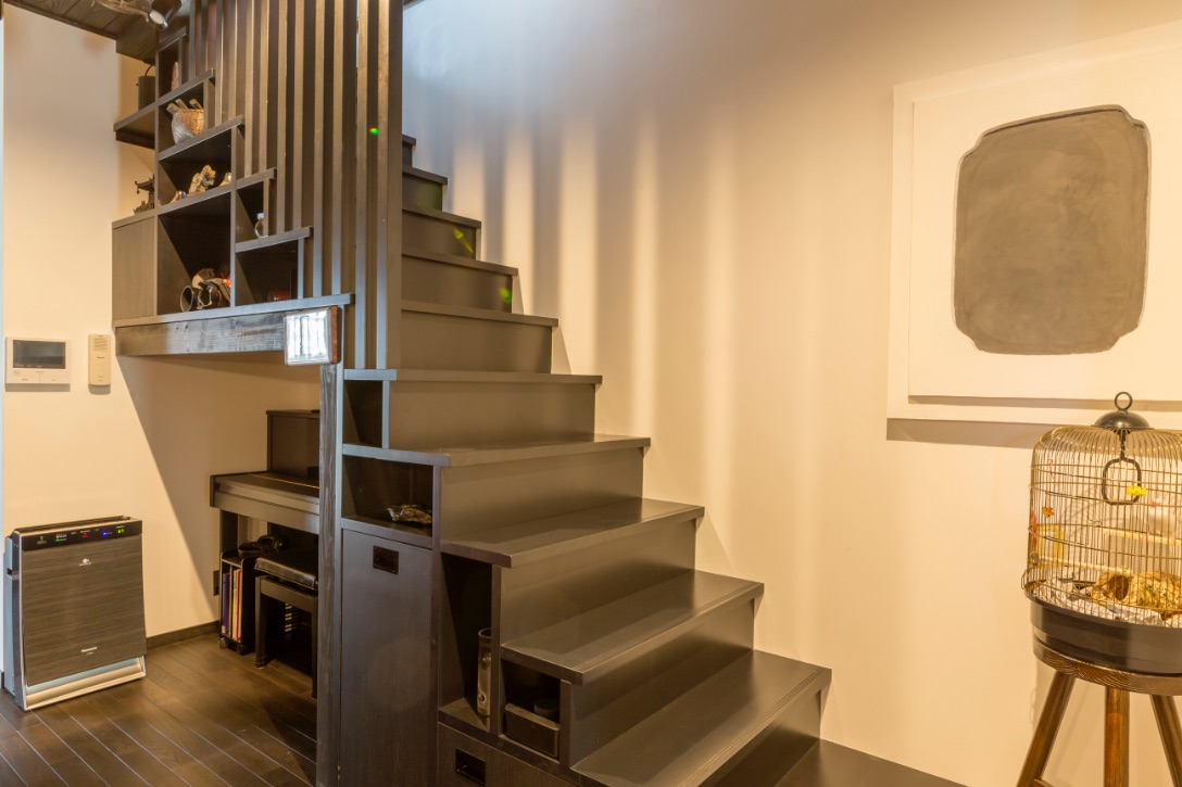 階段箪笥風のユニットを採用した階段。ステップ下はピアノスペースや飾り棚、収納棚に。ゴミ箱もここに隠しました。