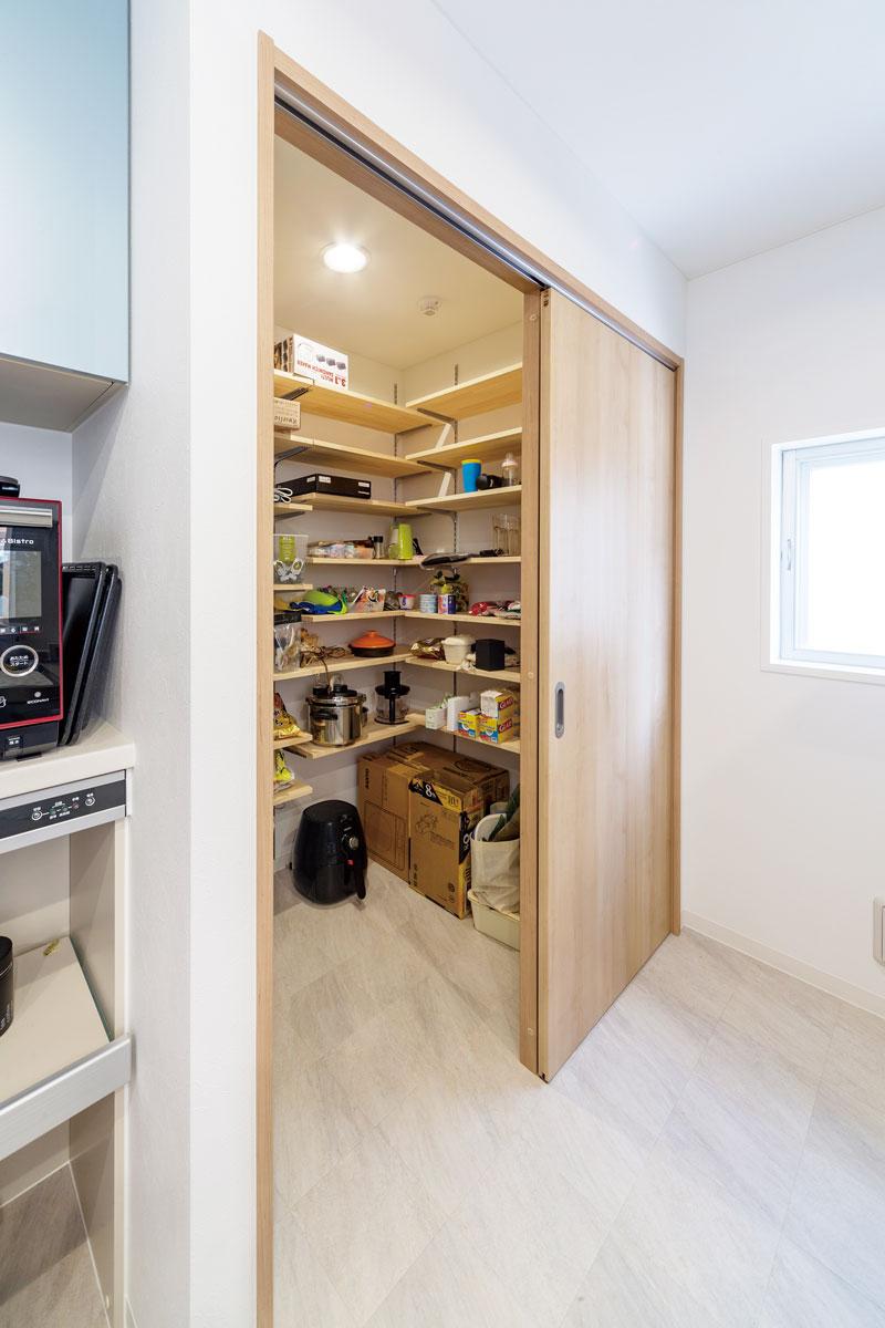 キッチン背面に設けたウォークインパントリーは、収納力はたっぷり&閉めればスッキリ