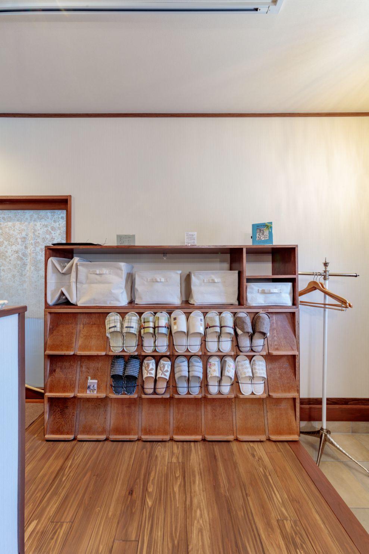 幼稚園の靴箱だったと思われる棚を、スリッパラックとして活用。横幅を合わせて造作したオープン棚を乗せて鞄置き場も設置。