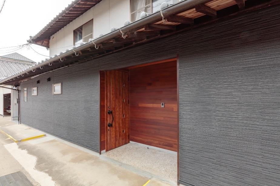 ダークグレーのサイディング張りの外壁に、玄関周りはドアに色調を合わせた木材を張りました。