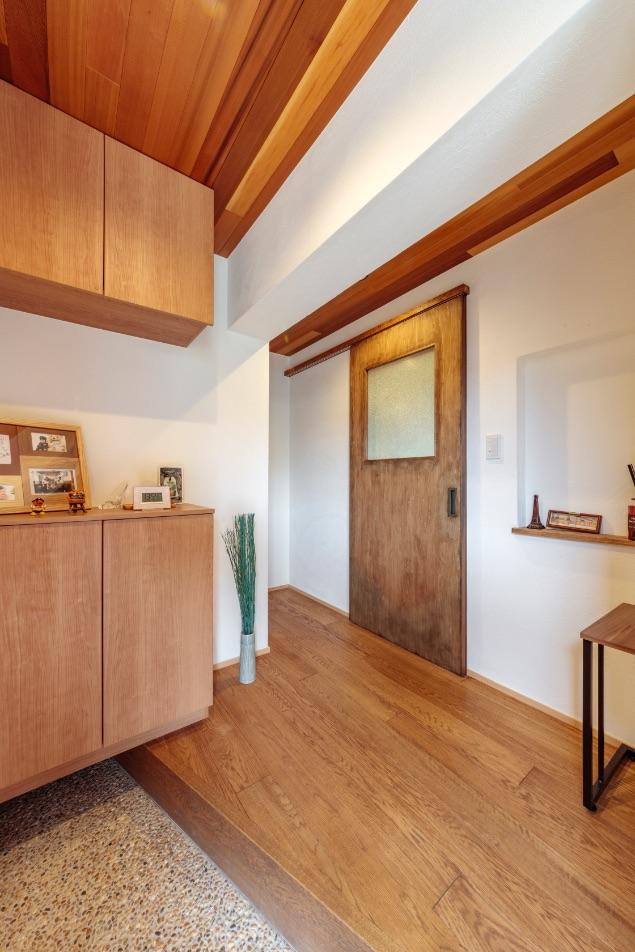 天然木と漆喰の自然素材で優しく迎え入れる玄関。土間は職人の技術を要する洗い出し仕上げ。