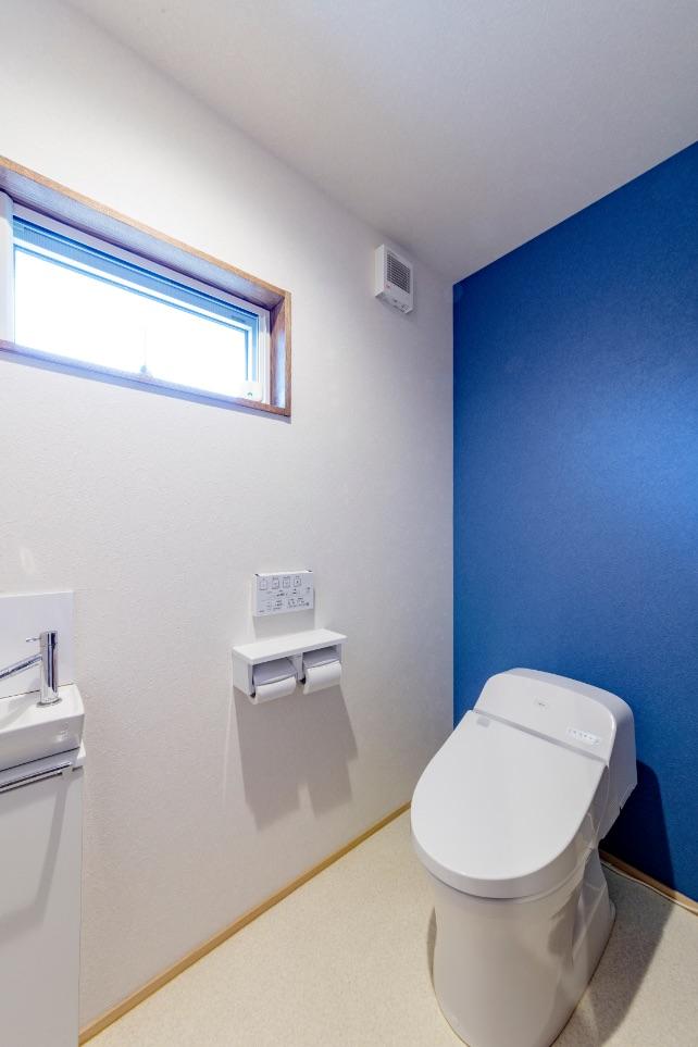 水廻りはすべて窓が取れる場所に設置。トイレは引き戸で出入りしやすく、ブルーを効かせて爽やかに。